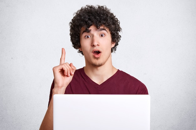 Surprised hipster guy keeps jaw dropped and fore finger raised, uses laptop computer, gets brilliant idea for creating new article, isolated on white concrete wall. people and technology