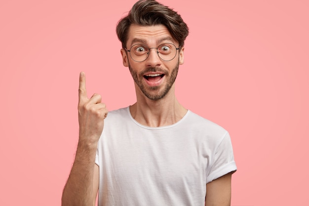 Surprised hipster with trendy haircut, has intriguing shocked gaze, points with index finger upwards, wears casual white t shirt and spectacles, isolated over pink wall