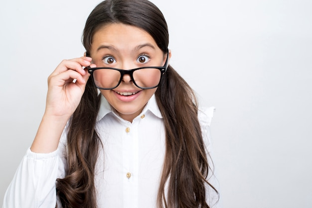 Surprised hispanic schoolgirl straightening glasses.