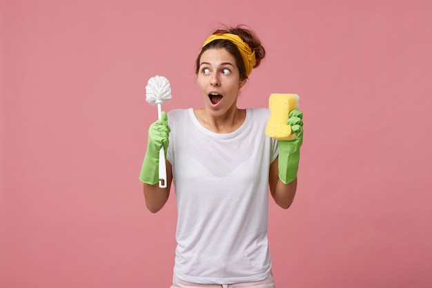 Surprised housewife in casual white t-shirt and protective gloves for cleaning going to tidy up room holding brush with sponge having puzzled look while remembering about her meeting with friend