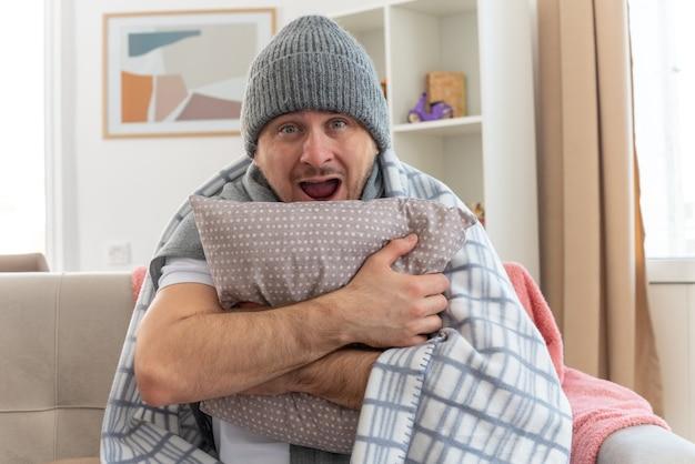 Sorpreso uomo malato con sciarpa intorno al collo indossando cappello invernale avvolto in plaid tenendo il cuscino seduto sul divano in soggiorno