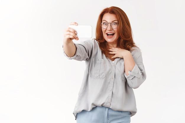 Sorpresa impressionata rossa donna di mezza età che parla di videochiamata smartphone reagendo entusiasta eccitata fantastica applicazione filtro fotocamera prendendo selfie stupito in piedi muro bianco