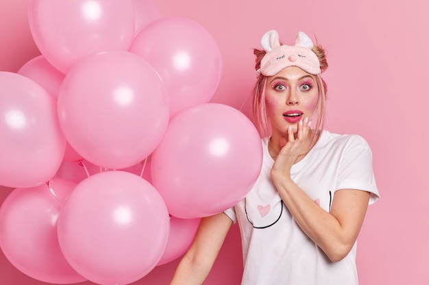 Surprised impressed young european woman with makeup wears sleepmask and casual t shirt holds inflated balloons celebrates birthday