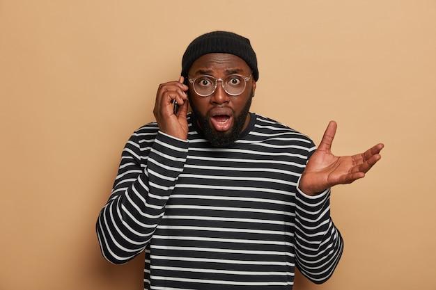 L'uomo nero sorpreso e indignato con la barba incolta ha una conversazione telefonica, riceve notizie perplesse su smartphone, fa gesti con il palmo