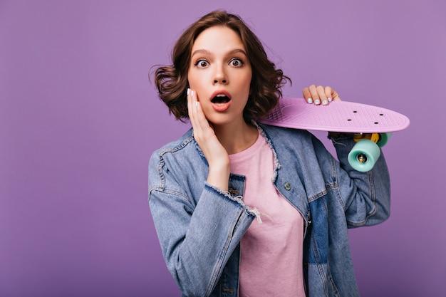 Donna ispirata sorpresa con gli occhi marroni in posa con lo skateboard. affascinante ragazza dai capelli scuri in piedi con la bocca aperta.