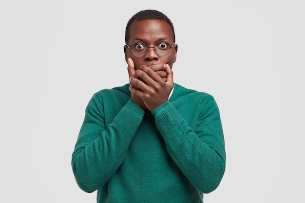 Удивленный напряженный темнокожий мужчина прикрывает рот ладонями, боится сказать слово, смотрит, носит прозрачные очки