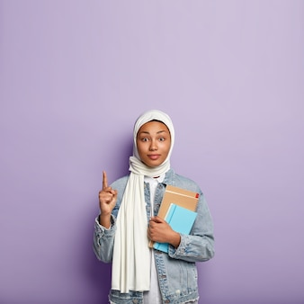 Surprised intriguing woman in headwear points upwards and looks with interest, shows blank space above for your advertisement or information, carries diary and spiral notebook. muslim religion