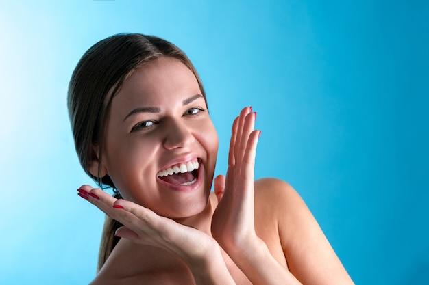 놀란 된 표정으로 놀된 즐거운 아름 다운 여성, bugged 눈으로 보이고 파란색 벽을 통해 입을 열어 둡니다. 인간의 반응과 감정
