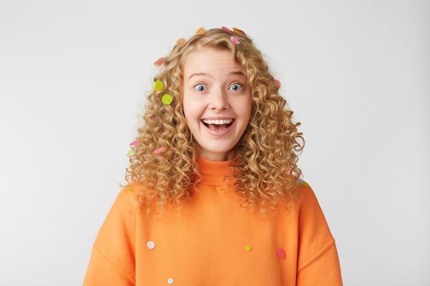 Удивленная, радостная, вдохновленная блондинка с широко открытыми голубыми глазами, счастливо улыбающаяся, чувствует себя довольной, одетая в оранжевый свободный свитер, изолированную на белой стене