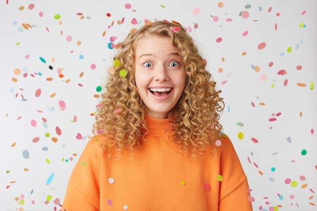 Удивленная, радостная, вдохновленная блондинка с широко открытыми голубыми глазами, счастливо улыбается, чувствует себя довольной, одетая в оранжевый свитер большого размера, стоит под падающим конфетти