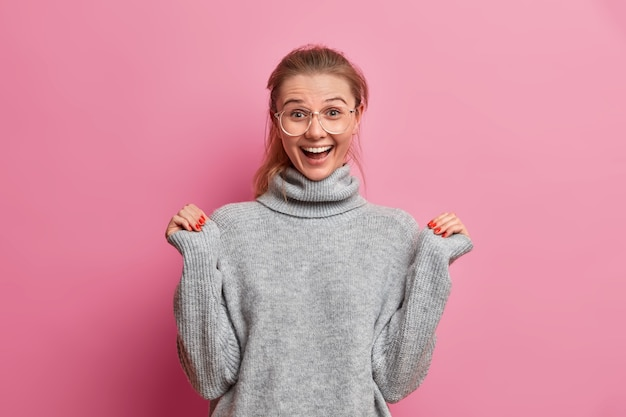 Удивленная радостная молодая европейка поднимает руки и с волнением смотрит, слышит что-то превосходное