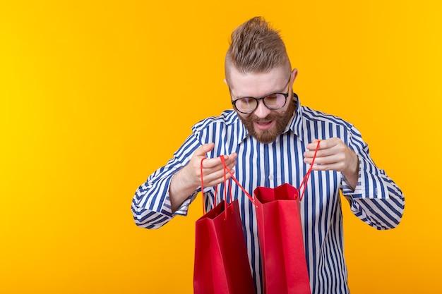 眼鏡とあごひげを持った驚きのうれしそうな若いハンサムな男が買い物のためにパッケージを調べます