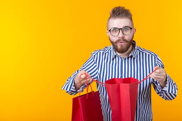 안경과 수염을 가진 놀란 즐거운 젊은 잘 생긴 남자가 쇼핑을 위해 패키지로 보입니다.