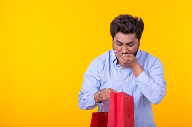 놀란 즐거운 젊은 남자가 쇼핑 패키지를 찾습니다
