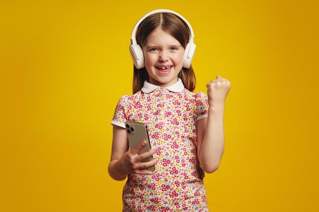 Удивленный ребенок в белых наушниках, использующий мобильный телефон, делает жест победителя
