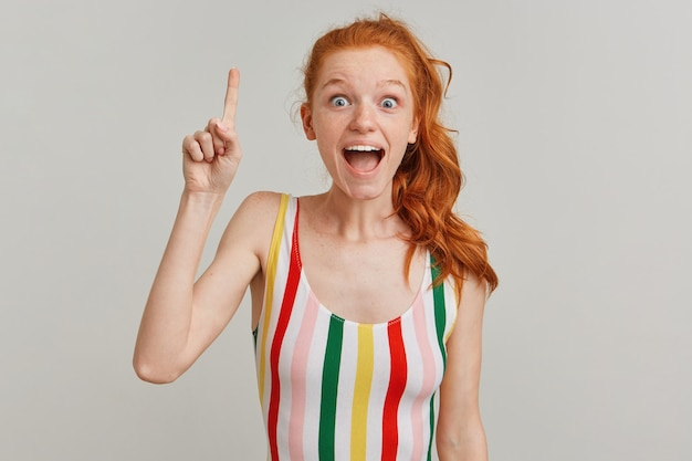 Surprised lady, amazed woman with ginger pony tail and freckles, wearing striped colorful swimsuit