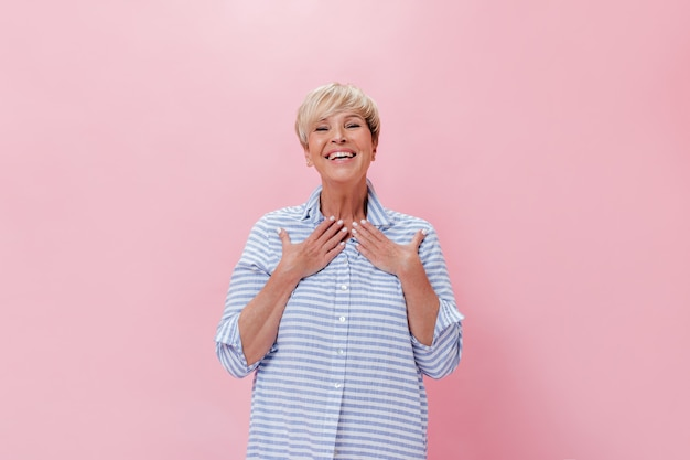 Surprised lady in blue outfit happily looks into camera on pink background