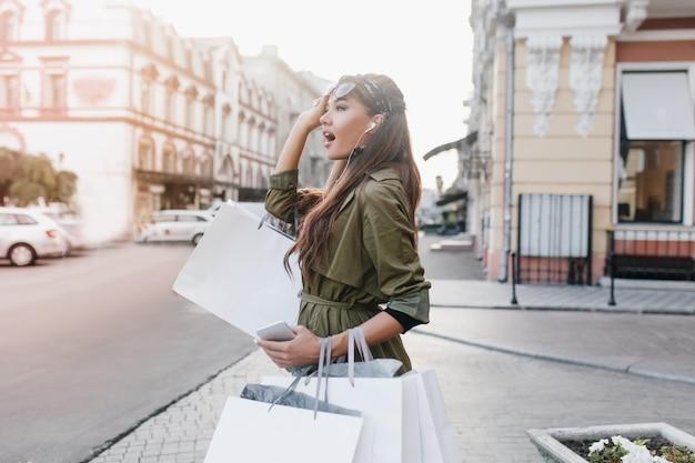 Удивленная дама в осеннем пальто смотрит в сторону, переходя дорогу