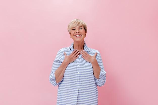 Удивленная дама в синем наряде радостно смотрит в камеру на розовом фоне