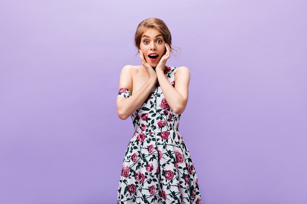 꽃 무늬 드레스에 놀란 여자는 카메라에 보인다. 보라색 배경에 포즈 유행 옷에 아름 다운 여자.