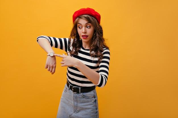 Удивленная дама в красном берете указывает на часы. милая молодая женщина с яркими губами и красивой шляпой позирует на оранжевом фоне.