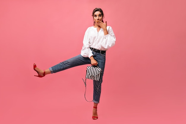 Surprised lady raises leg and poses with stylish handbag on pink background.  funny girl in long-sleeve blouse and in red high heels looks at camera. .