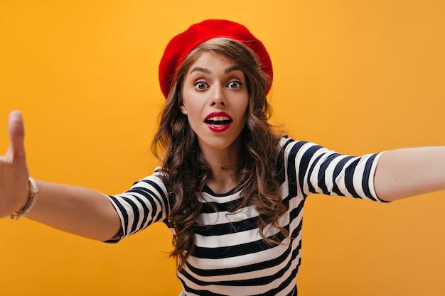 Signora sorpresa in berretto rosso fa selfie su sfondo arancione. donna moderna con capelli ricci con labbra luminose in vestiti a strisce in posa.