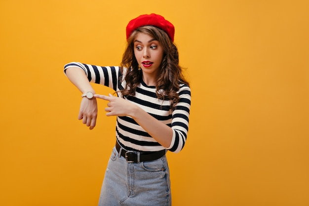 Surprised lady in red beret points to watch. cute young woman with bright lips and pretty hat posing on orange background.