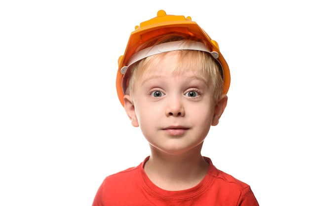 Surprised little blond boy in construction helmet and red t-shirt