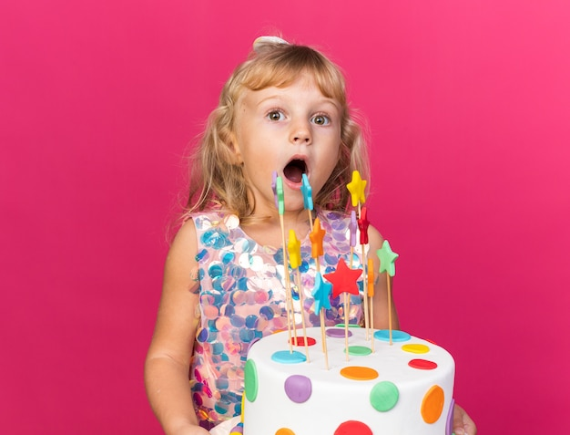 Sorpresa piccola ragazza bionda che tiene la torta di compleanno isolata sulla parete rosa con lo spazio della copia