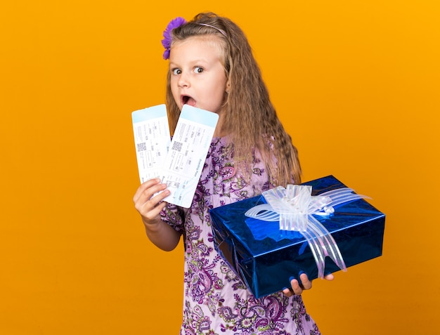 Surprised little blonde girl holding gift box and air tickets isolated on orange wall with copy space