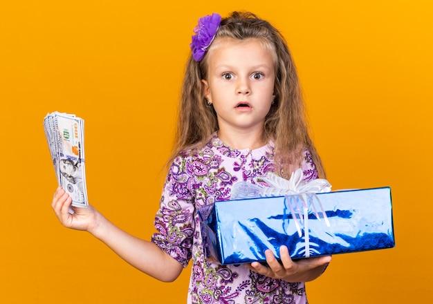 Удивленная маленькая блондинка держит подарочную коробку и деньги, изолированные на оранжевой стене с копией пространства