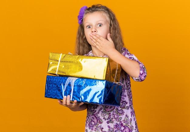 Bambina bionda sorpresa che mette la mano sulla bocca e che tiene i contenitori di regalo isolati sulla parete arancione con lo spazio della copia