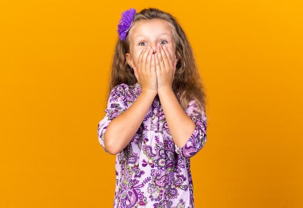 Piccola ragazza bionda sorpresa che si mette le mani sulla bocca isolata sulla parete arancione con spazio di copia