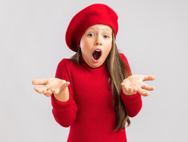 コピースペースで白い壁に隔離された空の手を示す正面を見て赤いベレー帽を身に着けている驚いた小さなブロンドの女の子