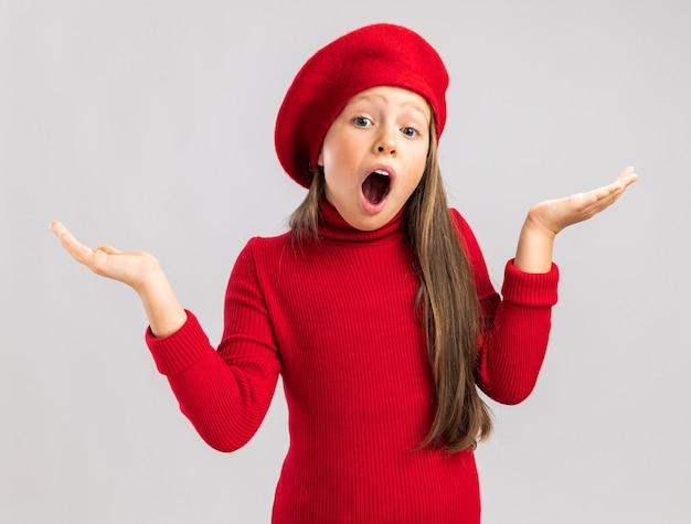 빨간 베레모를 쓴 금발 소녀가 복사공간이 있는 흰 벽에 격리된 카메라를 쳐다보며 허공에 빈 손을 보여주는 놀란 어린 금발 소녀