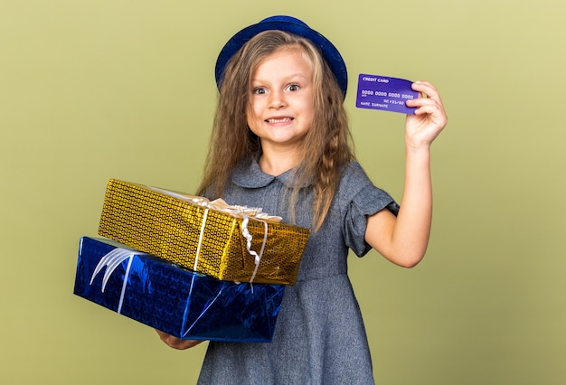 Surprised little blonde girl with blue party hat holding gift boxes and credit card isolated on olive green wall with copy space