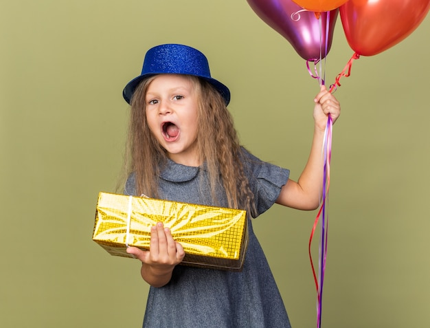 Surprised little blonde girl with blue party hat holding helium balloons and gift box isolated on olive green wall with copy space