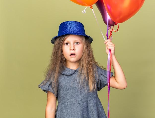 Bambina bionda sorpresa con il cappello blu del partito che tiene i palloni dell'elio isolati sulla parete verde oliva con lo spazio della copia