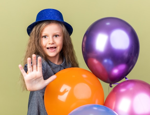 Sorpreso bambina bionda con cappello da festa blu in piedi con palloncini di elio gesticolando segnale di stop isolato sulla parete verde oliva con spazio di copia