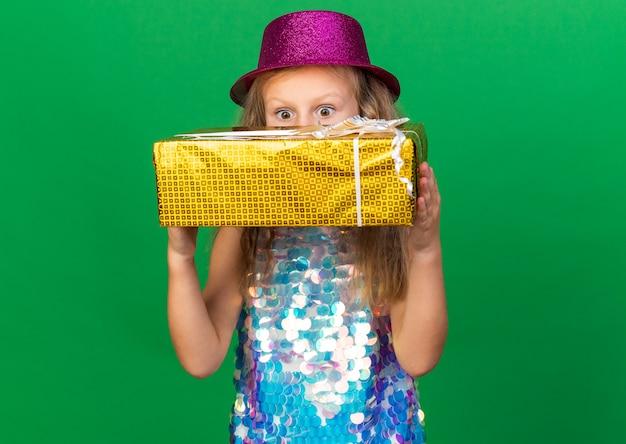 コピースペースと緑の壁に分離されたギフトボックスを保持している紫色のパーティハットで驚いた小さなブロンドの女の子