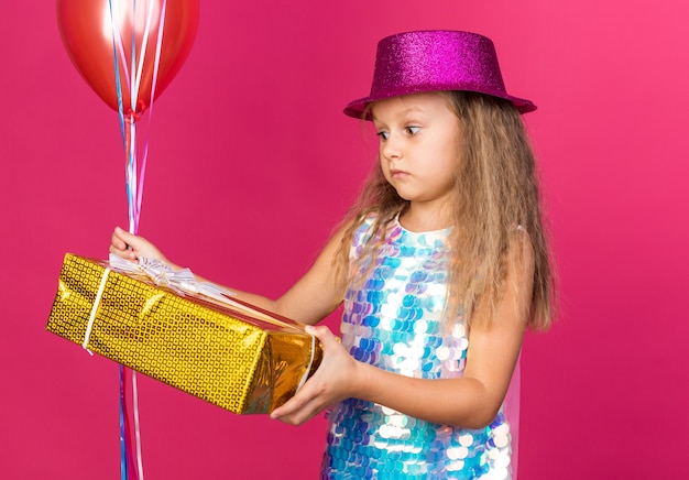 Surprised little blonde girl with purple party hat holding helium balloons and looking at gift box isolated on pink wall with copy space