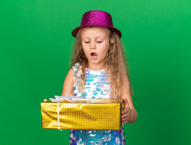 Surprised little blonde girl with purple party hat holding and looking at gift box isolated on green wall with copy space