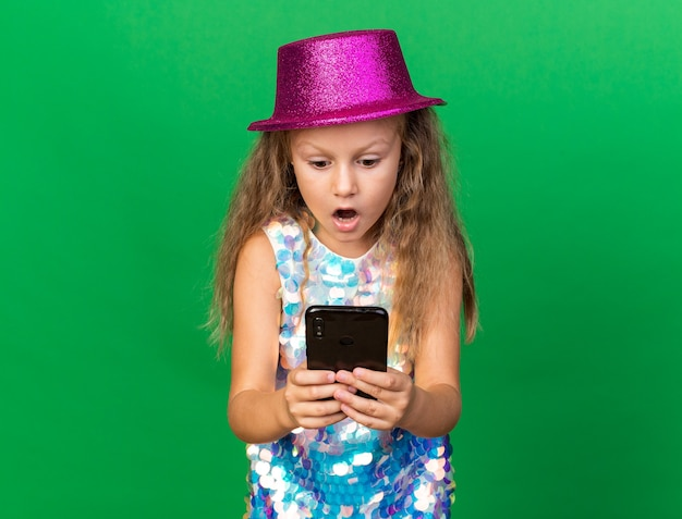 Surprised little blonde girl with purple party hat holding and looking at phone isolated on green wall with copy space