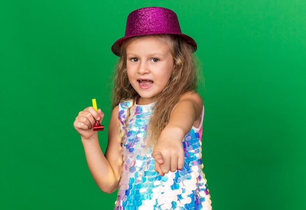 Surprised little blonde girl with purple party hat holding party whistle and pointing  isolated on green wall with copy space