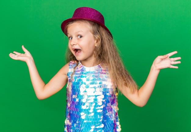コピースペースで緑の壁に隔離された手を開いたままにしておく紫色のパーティハットを持つ驚いた小さなブロンドの女の子