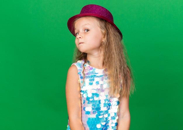 복사 공간 녹색 벽에 고립 된 측면을보고 보라색 파티 모자와 놀란 된 작은 금발 소녀