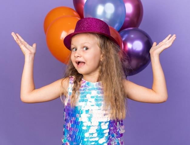 Sorpresa bimba bionda con cappello da festa viola in piedi con le mani alzate davanti a palloncini di elio isolati su parete viola con spazio di copia
