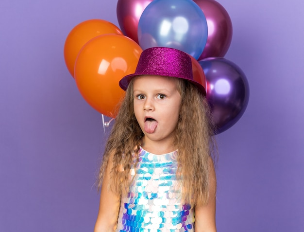 Surprised little blonde girl with violet party hat stucks out tongue standing with helium balloons isolated on purple wall with copy space