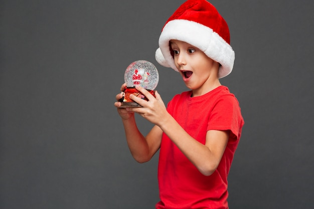 Surprised little boy child wearing christmas santa hat